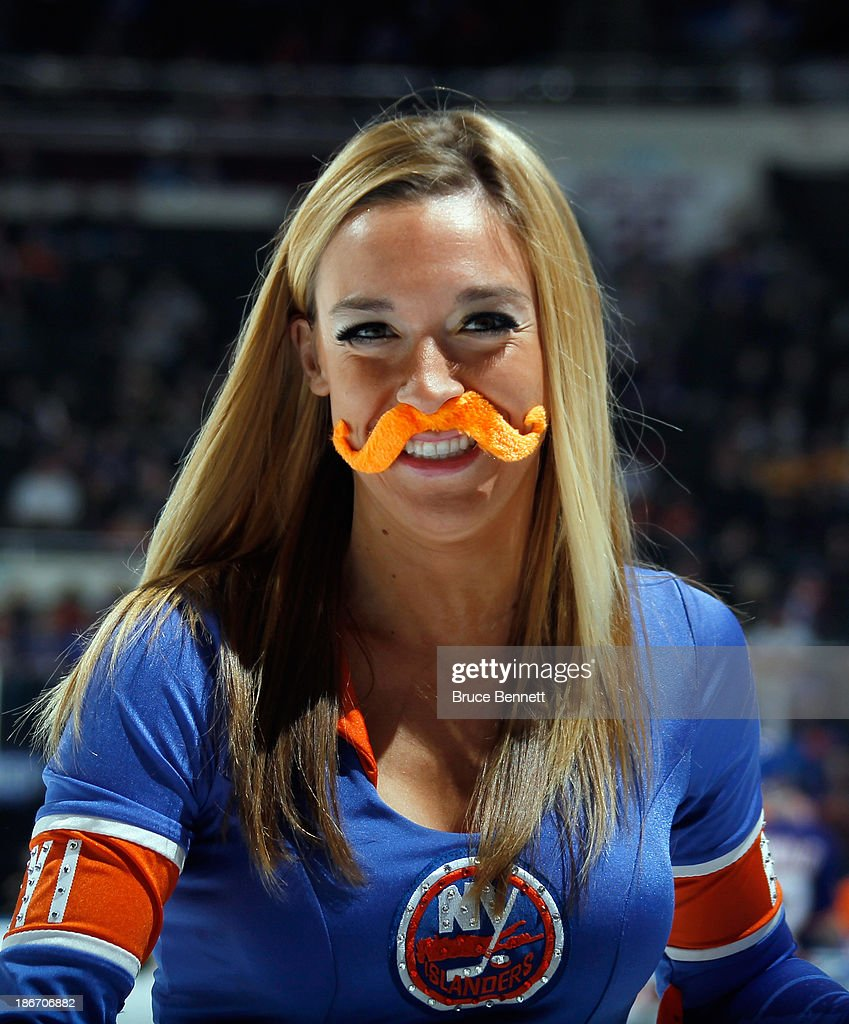 A New York Islander ice girl celebrates 'Movember' by wearing a fake mustache as she cleans the ice during the game between the New York Islanders and the Boston Bruins at the Nassau Veterans Memorial Coliseum on November 2, 2013 in Uniondale, New York.