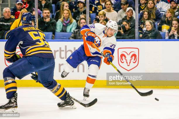 New York Islanders Center Anthony Beauvillier takes a shot as Buffalo Sabres Defenseman Rasmus Ristolainen defends during the New York Islanders and...