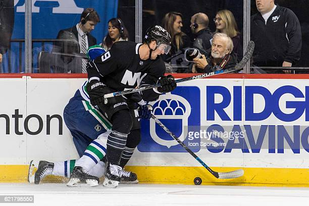 New York Islanders Center Brock Nelson sandwiches Vancouver Canucks Defenseman Alexander Edler into the boards during the second period a regular...