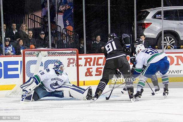 New York Islanders Center John Tavares passes the New York Islanders Winger Nikolay Kulemin who nets the puck past Vancouver Canucks Goalie Ryan...