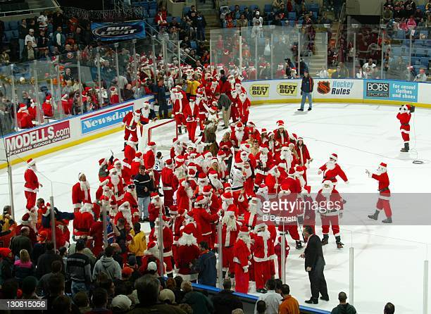 New York Islanders fans dressed as Santa Clause come onto the ice in the first period intermission during the Philadelphia Flyers and New York...