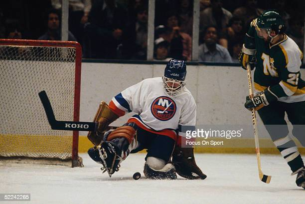 New York Islanders' goalie Billy Smith stretches to block a shot by the Minnesota North Stars during a game at the Nassau Coliseum circa 1981 in...