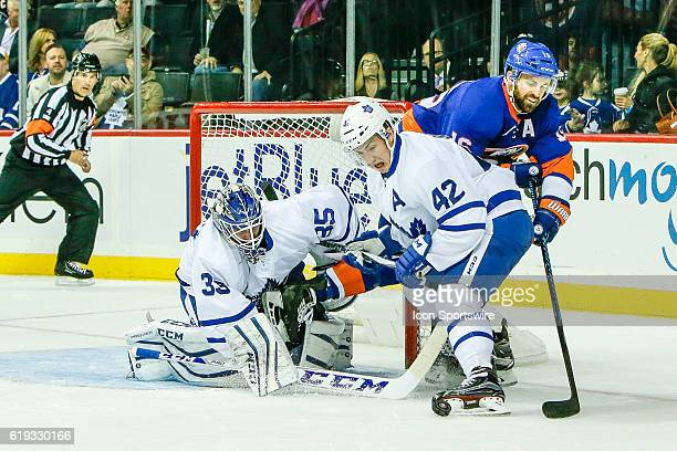 New York Islanders Left Wing Andrew Ladd attempts shot as Toronto Maple Leafs Center Tyler Bozak defends and Toronto Maple Leafs Goalie Jhonas Enroth...