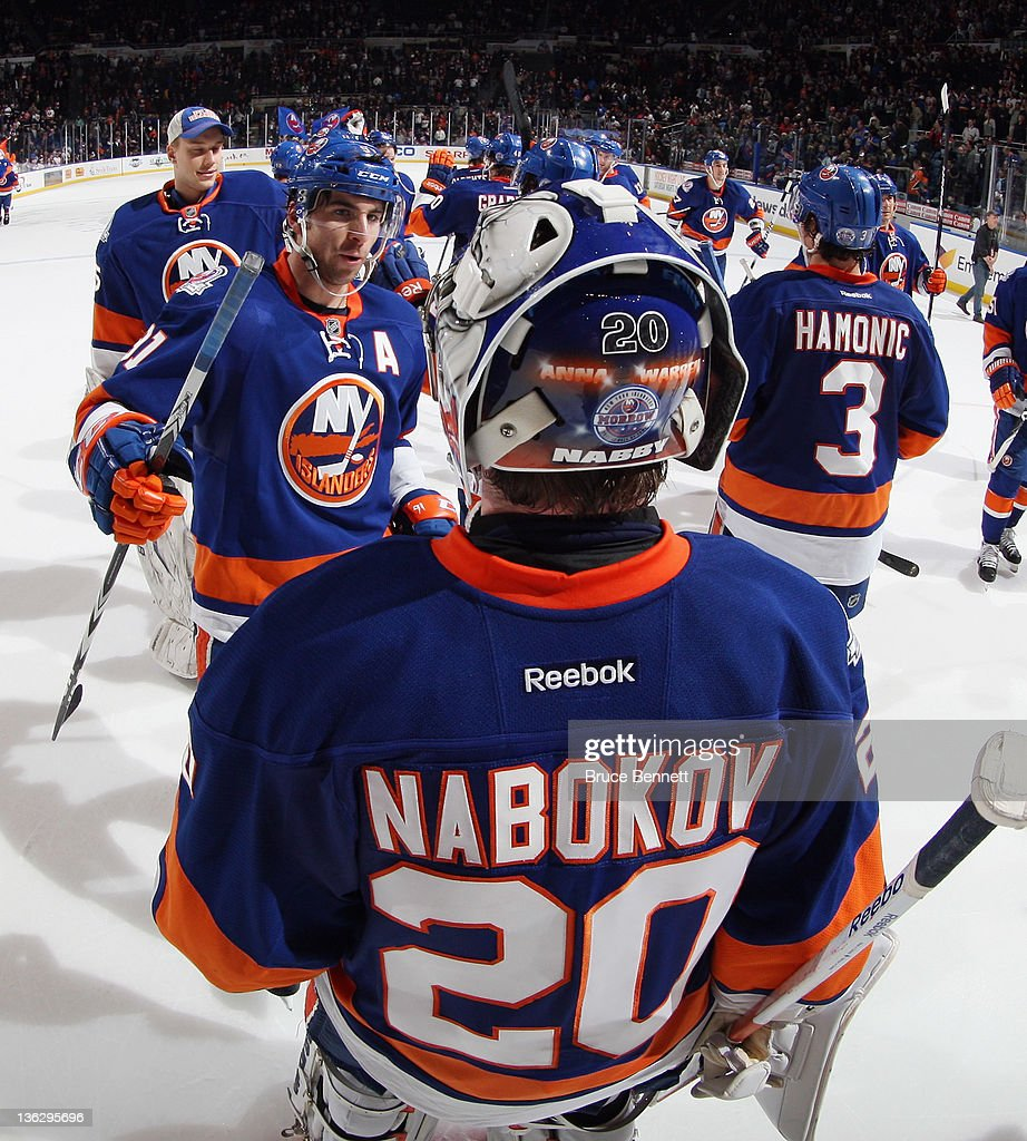 New York Islanders line up to congratulate <a gi-track='captionPersonalityLinkClicked' href=/galleries/search?phrase=Evgeni+Nabokov&family=editorial&specificpeople=171380 ng-click='$event.stopPropagation()'>Evgeni Nabokov</a> #20 following a 4-1 victory over the Edmonton Oilers at the Nassau Veterans Memorial Coliseum on December 31, 2011 in Uniondale, New York.