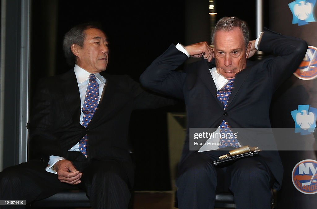 New York Islanders owner Charles Wang (L) assists New York Mayor Michael Bloomberg put on an Islanders tie after the announcement of the team's move in 2015 to Brooklyn at a press conference at the Barclays Center on October 24, 2012 in the Brooklyn borough of New York City.