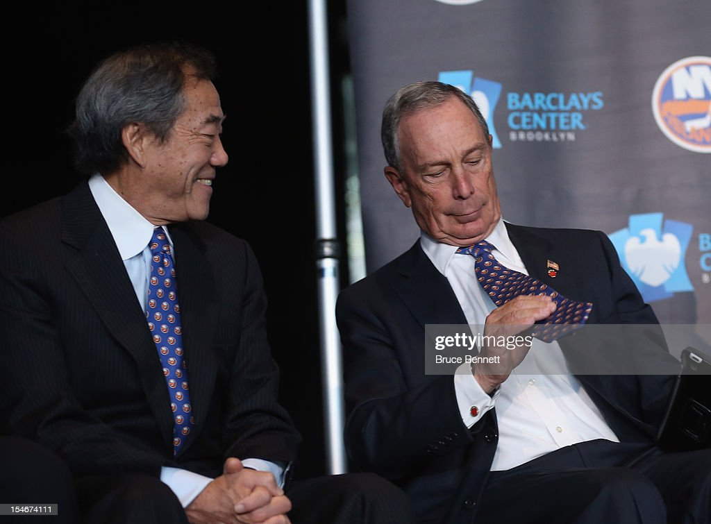New York Islanders owner Charles Wang (L) watches New York Mayor Michael Bloomberg put on an Islanders tie after the announcement of the team's move in 2015 to Brooklyn at a press conference at the Barclays Center on October 24, 2012 in the Brooklyn borough of New York City.