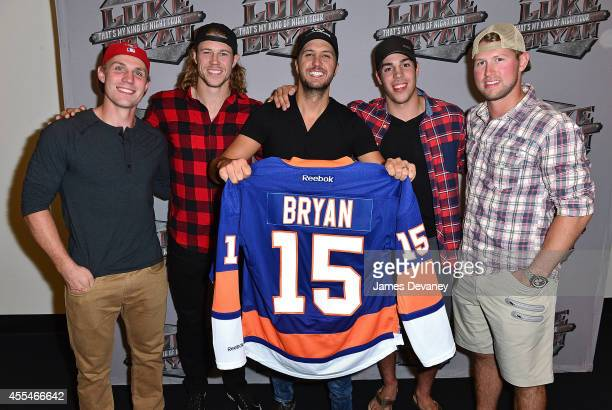 New York Islanders players Casey Cizikas Matt Martin Travis Hamonic and Josh Bailey present singer Luke Bryan with a personalized Islanders jersey...