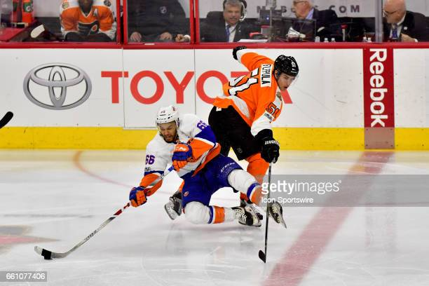 New York Islanders right wing Joshua HoSang makes the pass as he is tripped by Philadelphia Flyers center Valtteri Filppula during the hockey game...