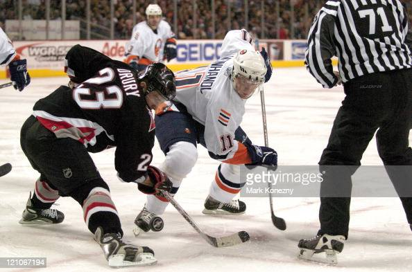 New York Islanders right wing Mattias Weinhandel and Buffalo Sabres center Chris Drury battle for the puck in a game at HSBC Arena in Buffalo New...
