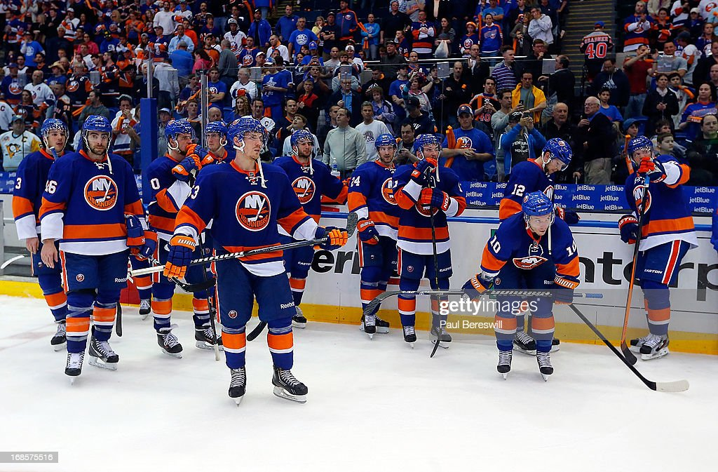 New York Islanders stand dejected on the ice as the Pittsburgh Penguins celebrate down the other end of the ice after the Islanders were eliminated from the playoffs in Game Six of the Eastern Conference Quarterfinals during the 2013 NHL Stanley Cup Playoffs at Nassau Veterans Memorial Coliseum on May 11, 2013 in Uniondale, New York. Penguins won 4-3 in overtime.
