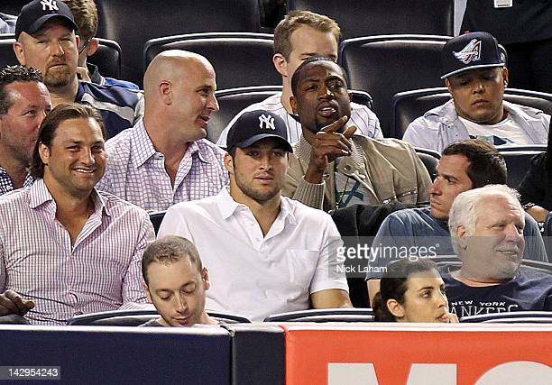 New York Jet quarterback Tim Tebow and Miami Heat's Dwyane Wade watch on during the game between the Los Angeles Angels of Anaheim and the New York...