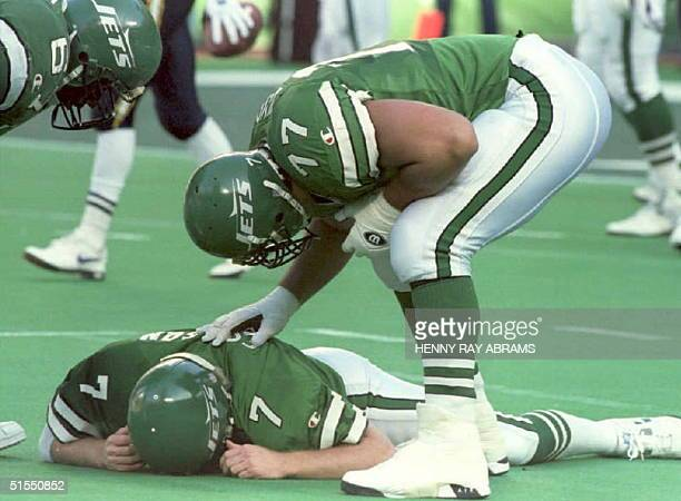 New York Jets' Matt Willig and Dwayne White check on their quarterback Boomer Esiason who was knocked down and suffered a concussion after throwing...