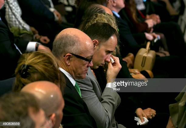 New York Jets owner Woody Johnson sits next to a man drying his eyes during the dedication ceremony in Foundation Hall at the National September 11...