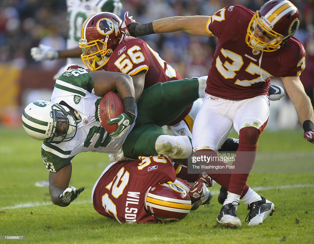 New York Jets running back Shonn Greene (23) is brought down by Washington Redskins inside linebacker Perry Riley (56), Washington Redskins cornerback Josh Wilson (26) and Washington Redskins free safety Reed Doughty (37) in the second quarter as the Washington Redskins play the New York Jets at FedEx Field in Landover MD, December 4, 2011.