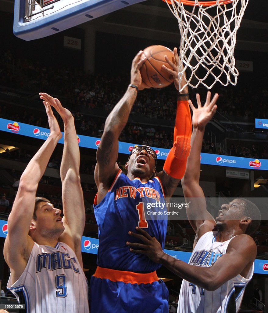 New York Knicks center Amar'e Stoudemire (1) grabs a rebound between the Orlando Magic's Nikola Vucevic (9) and Andrew Nicholson (44) in the second half at the Amway Center in Orlando, Florida, Saturday, January 5, 2013. The Knicks defeated the Magic, 114-106.