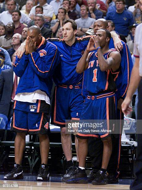 New York Knicks' Chris Dudley drapes his arms over teammates John Wallace and Andrew Lang as Chris Childs shouts to the court as Game 2 of the...