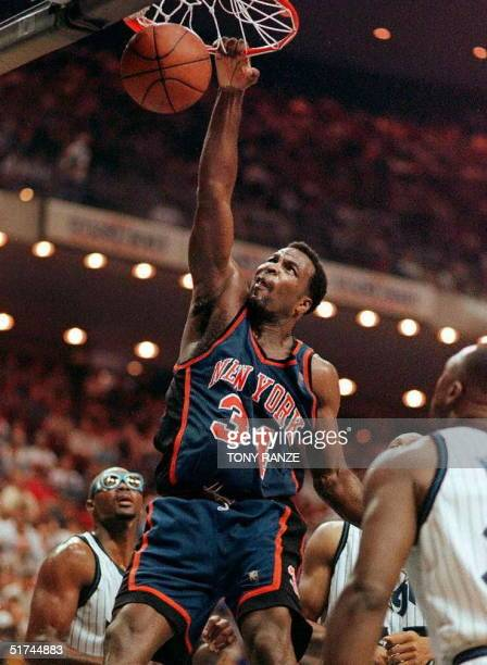 New York Knicks forward Charles Oakley slam dunks the ball after driving past Orlando Magic forward Horace Grant and guard Gerald Wilkins during the...