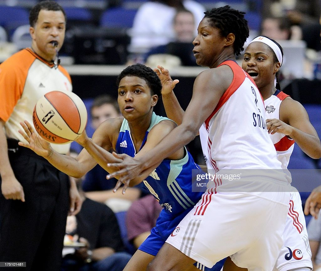 New York Liberty guard Kamiko Williams (4) passes out of a double team by Washington Mystics center Michelle Snow (2) and Mystics guard Ivory Latta (12), back, in the third quarter at the Verizon Center in Washington, D.C., Wednesday, July 31, 2013, The Liberty defeated the Mystics, 88-78.