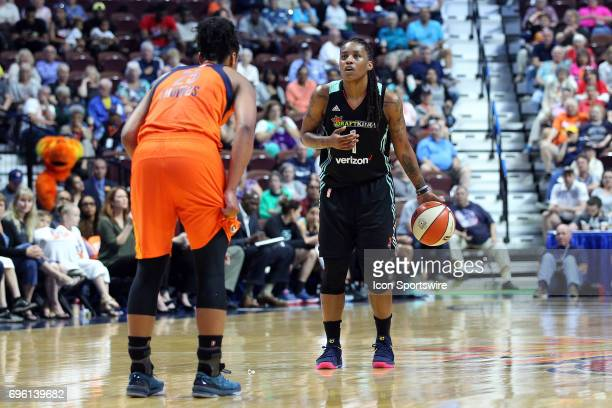 New York Liberty guard Shavonte Zellous glances at the game clock while defended by Connecticut Sun forward Alyssa Thomas during the second half of...