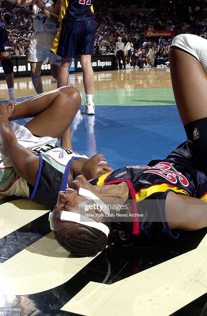 New York Liberty's Crystal Robinson and Indiana Fever's Tamika Catchings lie on the floor in pain after colliding under the basket in the second half...