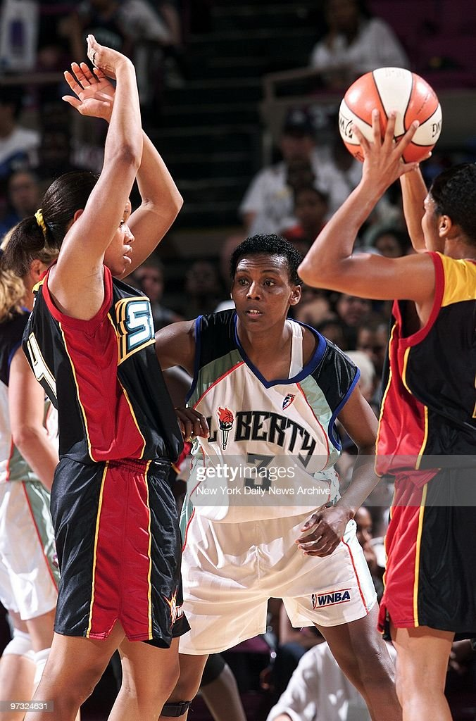 New York Liberty's Crystal Robinson gets sandwiched between two Detroit Shock players during action at Madison Square Garden The Shock went on to...