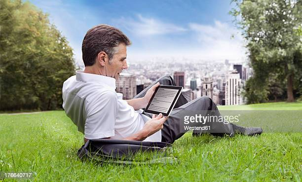 USA, New York, Man sitting on grass and using digital tablet, city in background