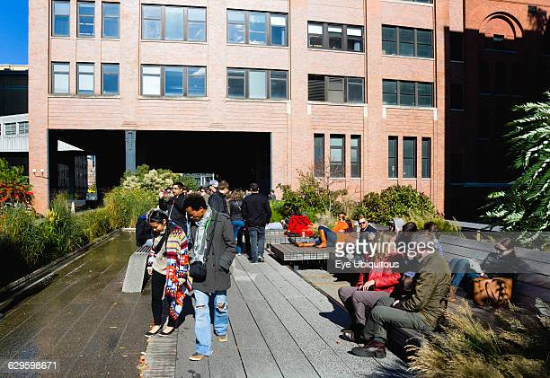 USA New York Manhattan people seated and walking beside the water feature on the Sundeck leading to the Chelsea Market Passage on the High Line...