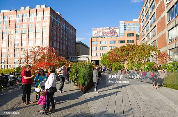 USA New York Manhattan people walking along a path beside plants in autumn colours on the sundeck leading to the Chelsea Market Passage on the High...