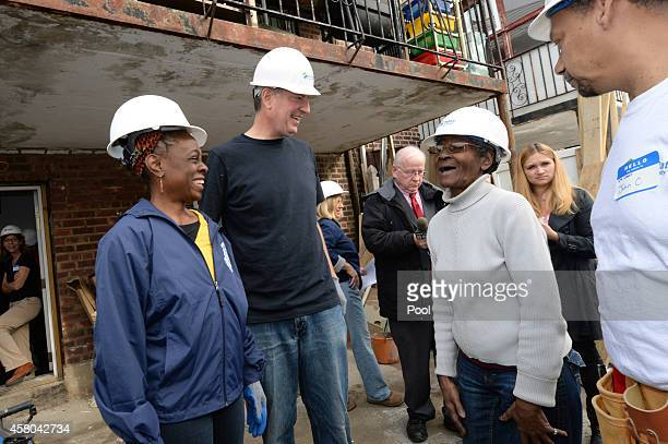 New York Mayor Bill de Blasio and wife Chirlane McCray talk with home owner Margurite Batts accompanied by Habitat for Humanities Construction...