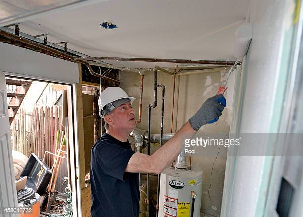 New York Mayor Bill de Blasio paints walls and trim inside the house as they help rebuild the home of Margurite Batts whose house was detroyed on the...