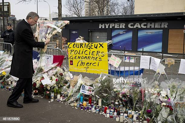 New York Mayor Bill de Blasio prepares to place flowers in front of the Hyper Cacher kosher supermarket in Paris on January 20 for the victims of the...