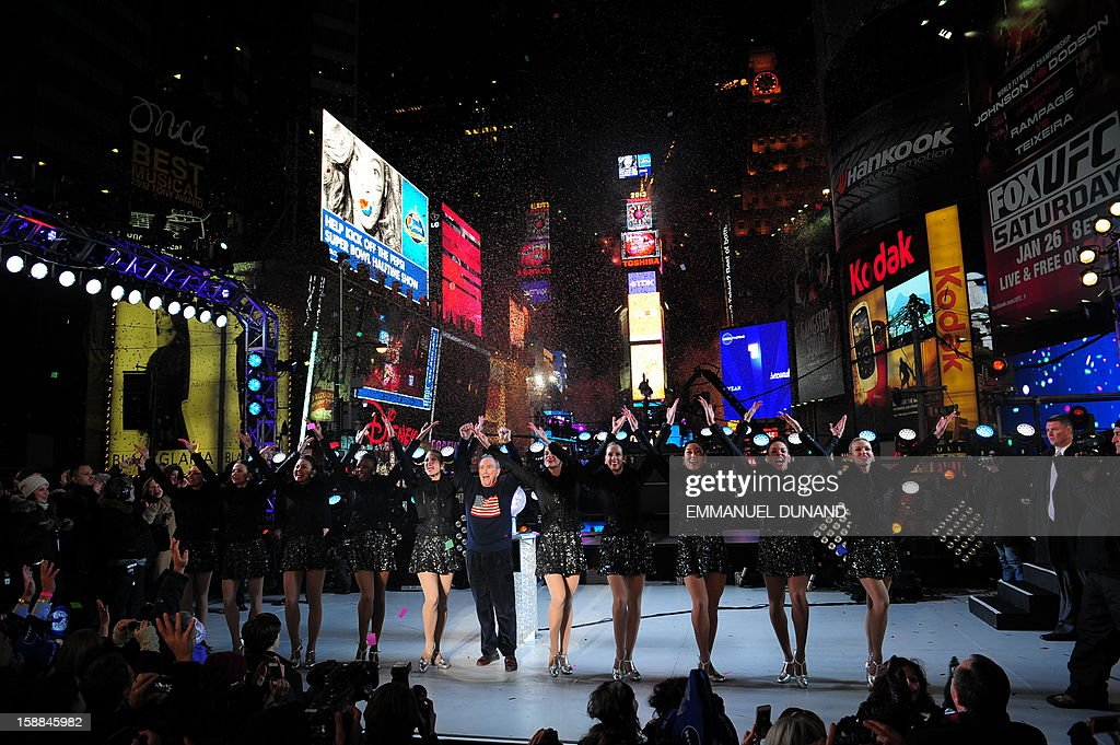 New York Mayor Michael Bloomberg and the Rockettes celebrate the New Year on Times Square in New York, January 1, 2013. A million people cheered in New York's Times Square as the traditional crystal ball dropped to mark the start of 2013, bringing a rolling global New Year's party that kicked off in Australia to US shores. AFP PHOTO/EMMANUEL DUNAND