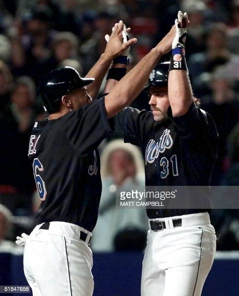 New York Mets' catcher Mike Piazza and rightfielder Derek Bell celebrate after Piazza's tworun home run in the bottom of the fifth inning 12 May 2000...