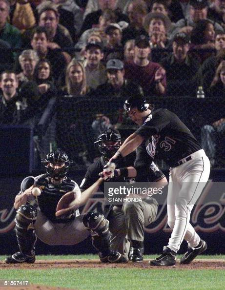 New York Mets' catcher Mike Piazza hits a homerun in the bottom of the third inning of Game Four of the World Series at Shea Stadium 25 October 2000...