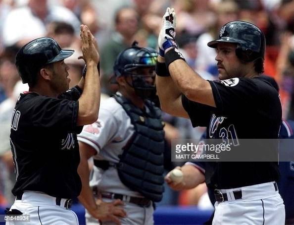 New York mets catcher Mike Piazza is congratulated by second baseman Edgardo Alfonzo after Piazza's tworun home run the Mets sixth straight hit of...