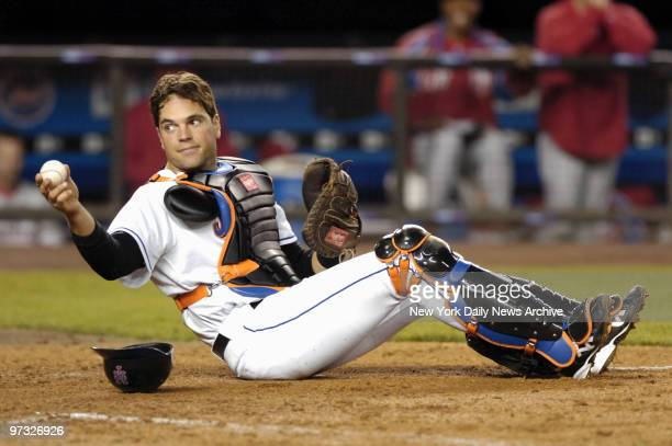 New York Mets' catcher Mike Piazza shows the home plate umpire he still has possession of the ball after placing the tag on Philadelphia Phillies'...