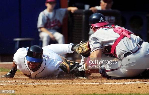 New York Mets' center fielder Jay Payton is tagged out by Atlanta Braves' catcher Javy Lopez after trying to score on a suicide squeeze in the fifth...