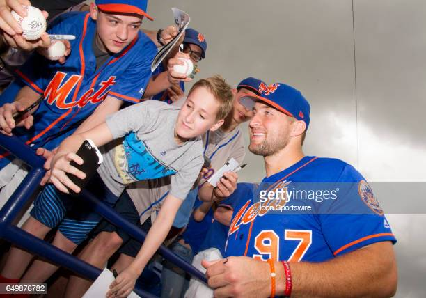 New York Mets Designated Hitter Tim Tebow smiles and takes a photo with a female fan before the start of an MLB spring training game between the...