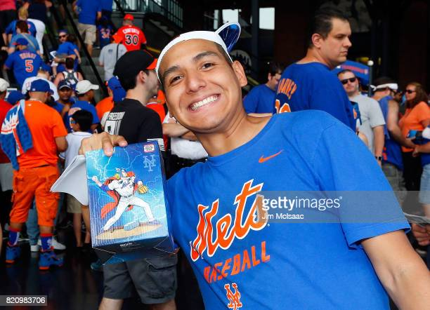 New York Mets fan Charlie Correa poses for a photograph after receiving his Noah Syndergaard bobblehead prior to a game between the Mets and the...