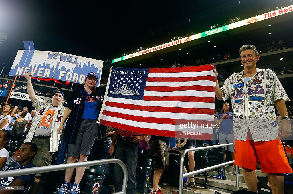 New York Mets fans hold a flag and banner in reference to September 11th 2001 during the seventh inning stretch of a game between the Mets and the Washington Nationals at Citi Field on September 11, 2013 in the Flushing neighborhood of the Queens borough of New York City.