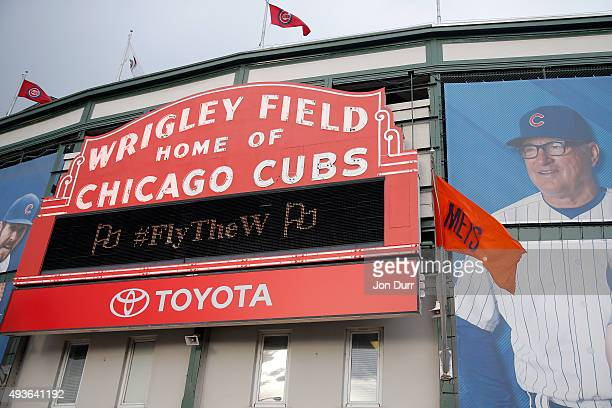 New York Mets flag flies in front of a Wrigley Field sign in front of the stadium prior to game four of the 2015 MLB National League Championship...