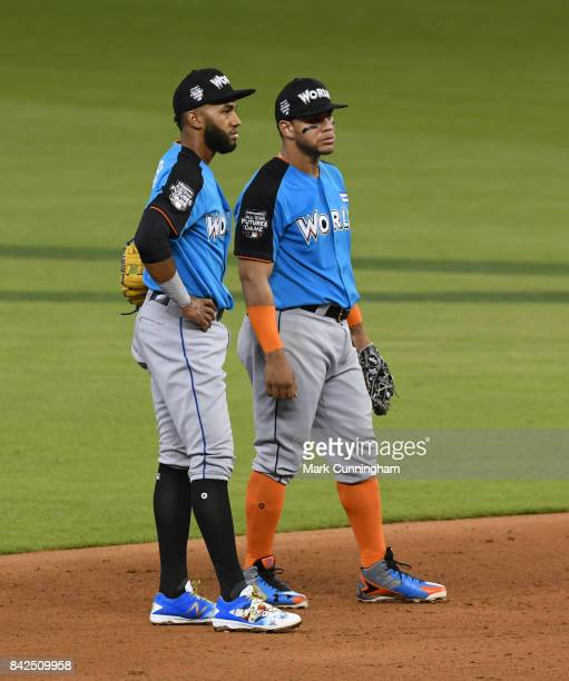 New York Mets prospect Amed Rosario and Chicago White Sox prospect Yoan Moncada of the World Team stand together on the field during the 2017...