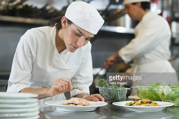 USA, New York, New York City, Chef and cook preparing food in commercial kitchen