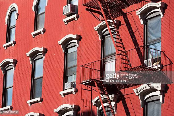 USA, New York, New York City, Facade of red building with fire escape