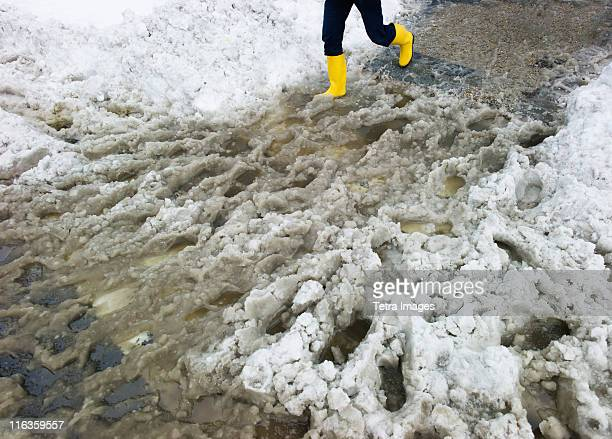 USA, New York, New York City, legs of person in yellow rubber boots walking in slush