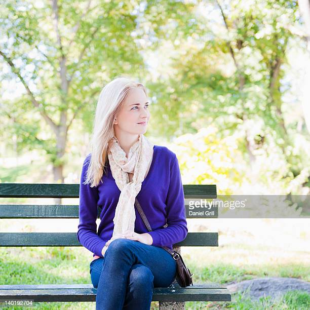 USA, New York, New York City, Manhattan, Central Park, Young woman sitting on bench