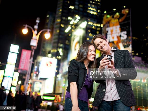 USA, New York, New York City, Manhattan, Times Square, smiling  young couple watching photos on digital camera