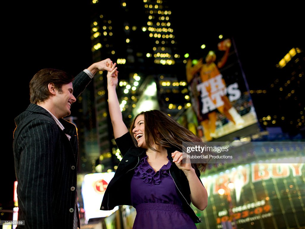 USA, New York, New York City, Manhattan, Times Square, smiling  young couple dancing in street : Stock Photo