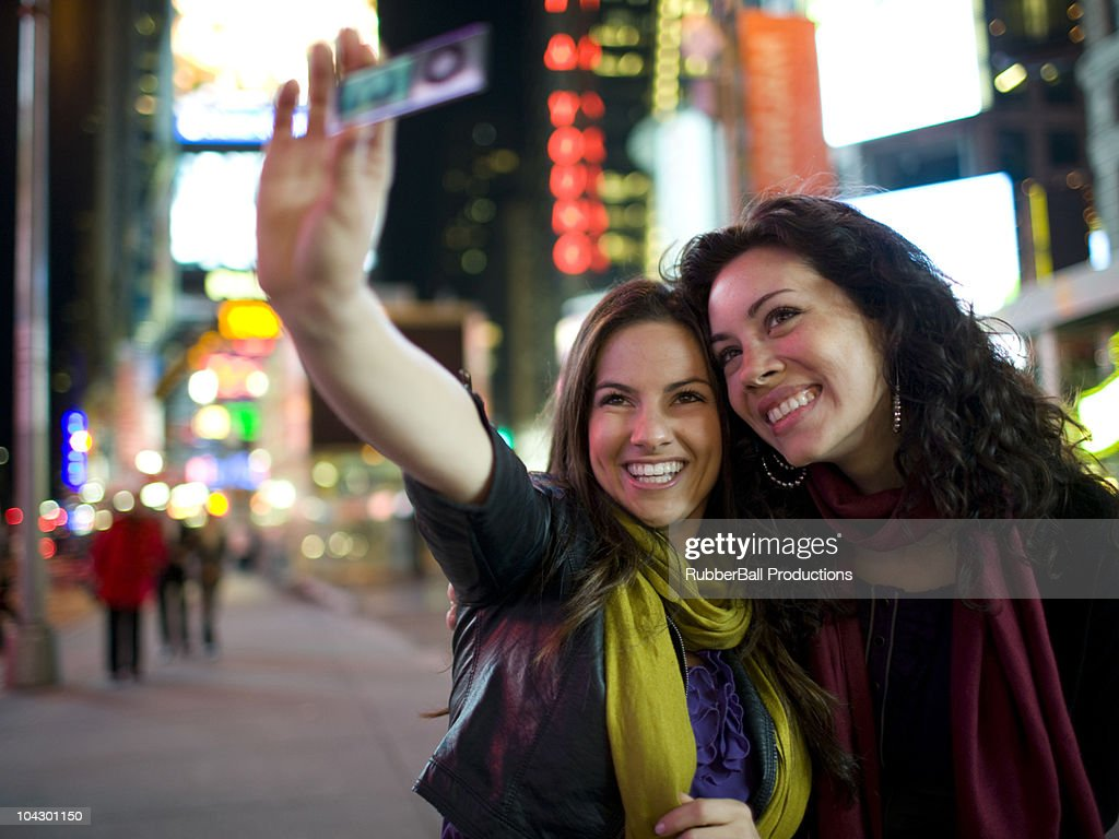 USA, New York, New York City, Manhattan, Times Square, two young women taking photos with mobile phone in street : Stock Photo