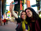 USA, New York, New York City, Manhattan, Times Square, two young women taking photos with mobile phone in street